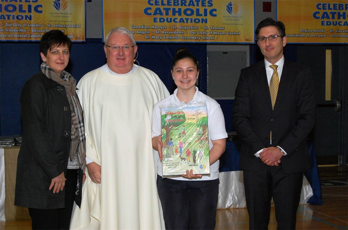 This year's Catholic Education Week commemorative plaque was designed by Sofia Cumuric, a grade 7 student at St. Martin of Tours Catholic Elementary School. Sofia and her mother were presented with a plaqued copy of her poster by the Very Rev. Father O'Mahony and Catholic Education Week Committee Co-chair Adrian DeTullio.