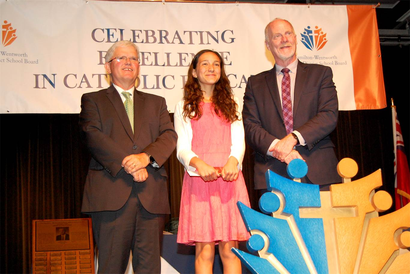 Chairperson Patrick Daly, left, and Director of Education David Hansen present St. Joachim student Michaela Tassone with a Sr. Maria Cordis Music Award.